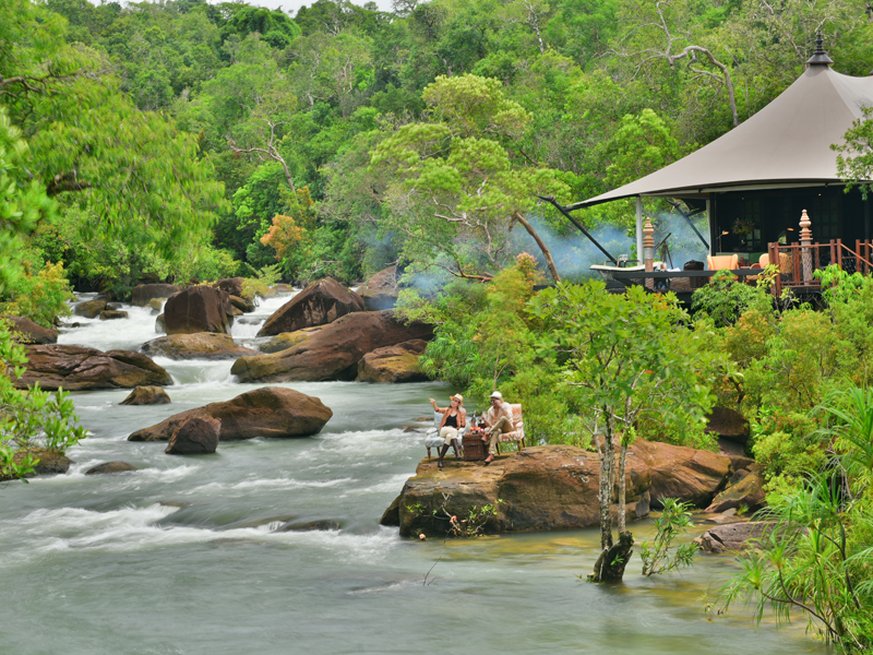 luxury eco resorts in southeast asia - Shinta Mani Wild - travelers resting along the river